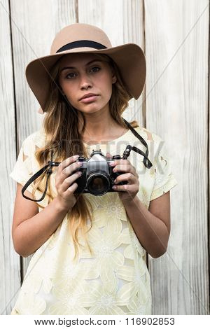 Calm young woman posing while holding a camera
