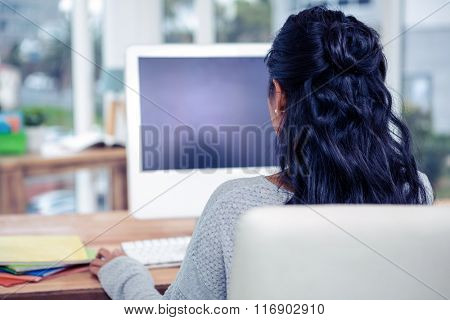 Rear view of woman using computer in office