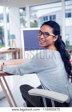 Smiling Asian woman using digital board looking back at the camera in office