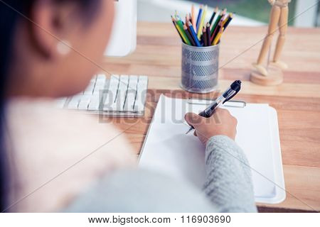 Over shoulder view of woman writing on white sheet in office