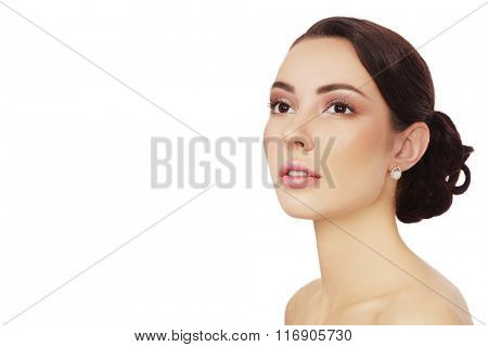 Portrait of young beautiful woman with clean make-up and prom hairdo looking upwards over white background, copy space