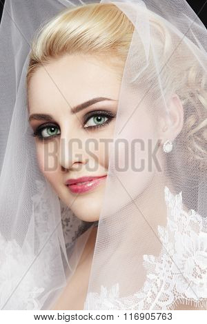 Portrait of young beautiful happy smiling bride with stylish make-up and bridal veil