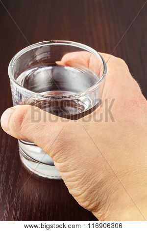 Hand Holding Glass Of Transparent Purified Water On Wooden Table