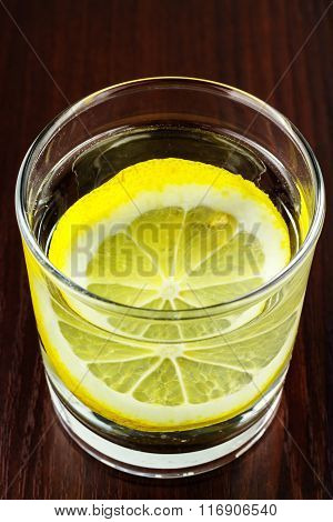Glass Of Transparent Purified Water With Slice Of Lemon, On Wooden Table
