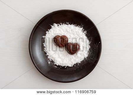 Two Chocolate Heart-shaped Candies On A Brown Plate With Sugar Powder Against Wooden Background