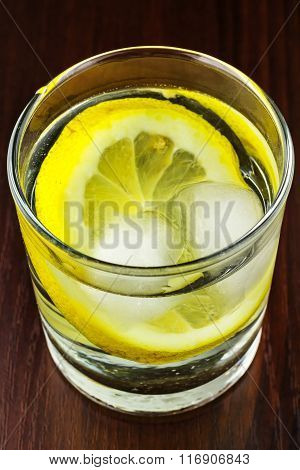 Glass Of Transparent Purified Water With Slice Of Lemon And Ice, On Wooden Table