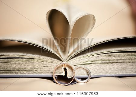 Wedding ring about an open book with pages in the shape of a heart
