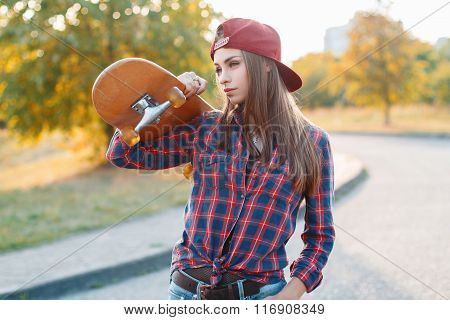 Young Beautiful Woman Holding A Skateboard In The Park At Sunset