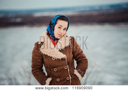Young  charismatic attractive  woman clothed sheepskin coat and scarf. Girl looks at camera near big
