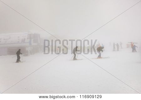 People Skiing On Extreme Weather With Fog And Zero Visibility