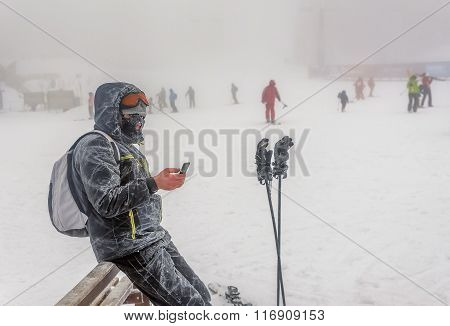 Man Standing Outdoor On The Snow And Fog And Texting On Smartphone
