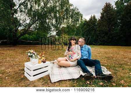 Pregnant Beautiful Woman With Her Handsome Husband Sweetly Resting Outdoors In The Autumn On Picnic.
