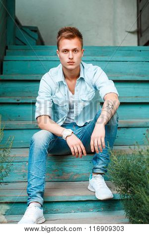 Young Man In Denim Clothes Sitting On Wooden Stairs