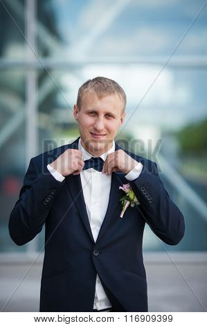 Gorgeous Elegant Groom In Stylish Blue Suit Tying A Bowtie On The Background Of Modern Building
