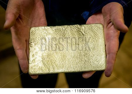Raw gold ingot in the hands