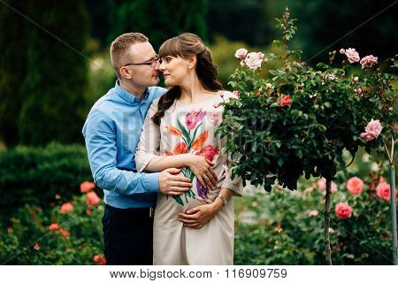 Pregnant Beautiful Woman And Her Handsome Husband Lovely Hugging In Park.