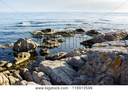Sea Wave Breaks About Rocky Shore At Sunrise