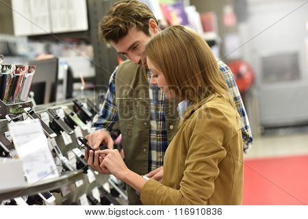Department store seller assisting customer with buying new phone