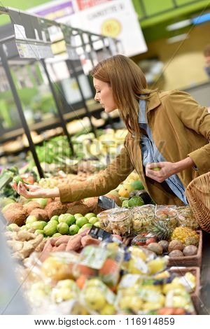 Woman at the grocery store buying fruits and vegetables