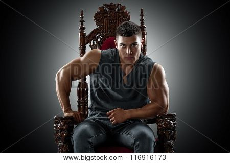 Muscular young man in a T-shirt and jeans, sitting on the throne.