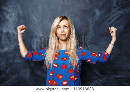 Young Beautiful Girl Shows The Strength And Looking Up On A Dark Background