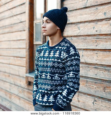 Young Handsome Guy In Winter Christmas Sweater On The Background Of A Wooden House. Man Resting In T