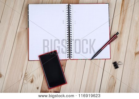 Smart Phone And Notepad On Desk