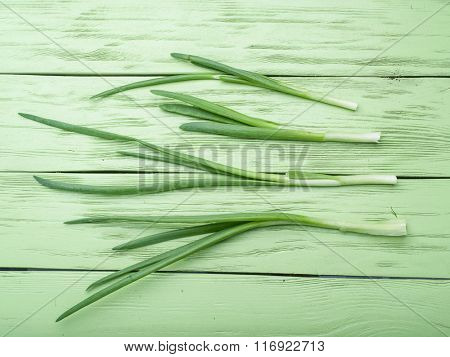Green onion on the wooden background.