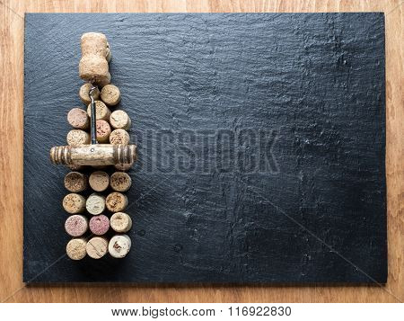 Wine corks in the shape of wine bottle on the graphite background.