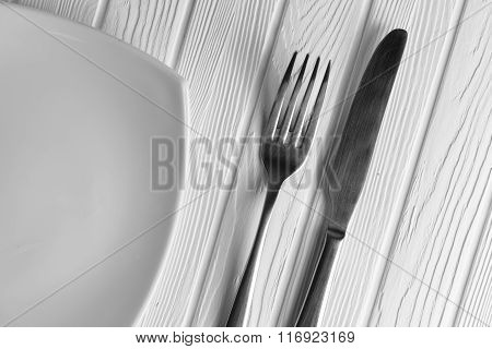Empty Plate, Fork And Knife On Wood Background