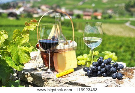 Two wineglasses, grapes and cheese against vineyards. Switzerland