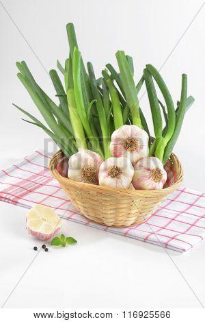 basket of fresh garlic bunch on checkered dishtowel