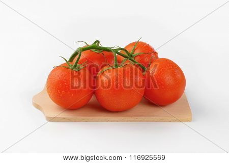 bunch of washed tomatoes on wooden cutting board