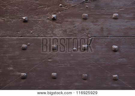 Brown painted wooden gate fixed with rivets. Background texture.