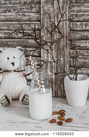Almond Milk In A Glass Bottle, Almonds And A Toy Bear On A Light Wooden Table. Still Life In A Vinta
