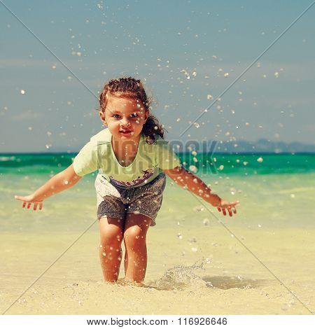 Happy Enjoying Kid Girl Playing And Splashing With Water On Blue Sea Background