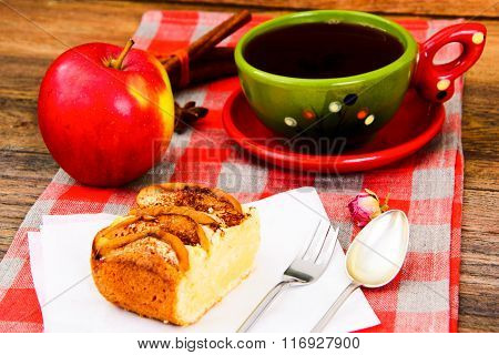 Apple Pie with Tea Cup on Woody Background.