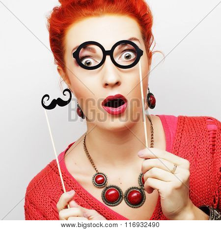 woman holding mustache and glasses on a stick.