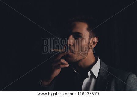 Handome Confident Man In Suit On The Black Background Smoking A Cigar