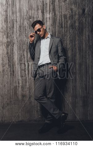 Stylish Man With Glasses Holding Hand In A Pocket On The Grey Background