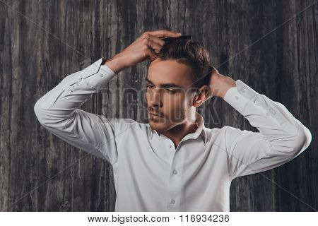 Attractive Rigid Man Combing Hair On The Grey Background