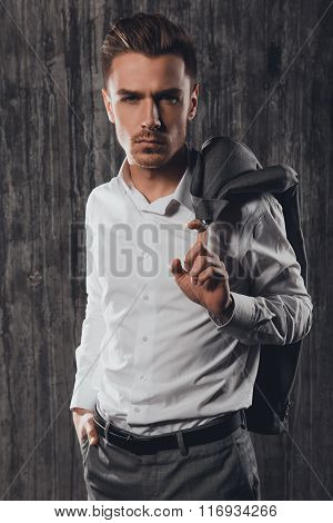 Attractive Rigid Man Holding Jacket On A Shoulder On The Grey Background