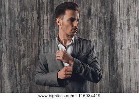 Handome Man In Suit On The Grey Background Fastening Buttons On The Sleeves
