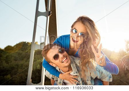 Positive Funny Couple In Love On The Bridge Gesturing Two Fingers