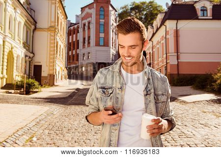 Cheerful Happy Man Typing Sms And Holding Cup Of Coffee