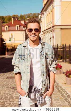 Cheerful Smiling Boy In Spectacles Holding Hands In Pockets Of Jeans