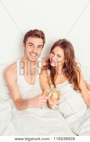 Happy Smiling Couple In Love At Home Embracing Each Other With Champagne