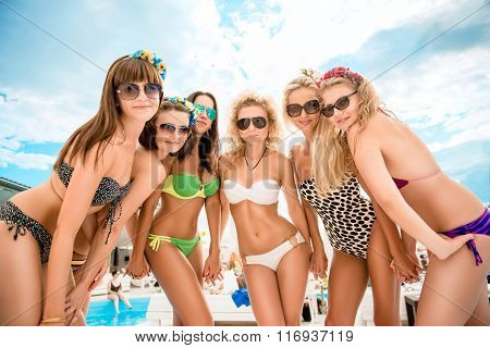 Pretty Girls With Glasses And  Swimsuits Relaxing By The Pool At The Resort