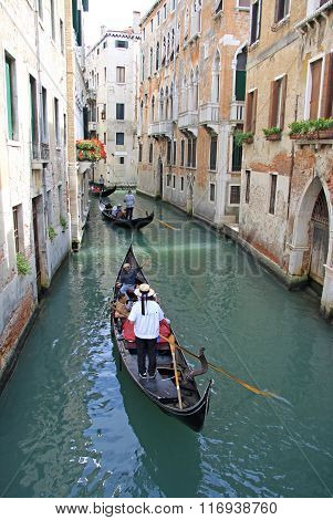 Venice, Italy - September 02, 2012:  Gondolier Rides Gondola In A Narrow Channel, Venice, Italy