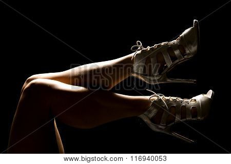 A Woman's Legs Up Highlighted In Heels
